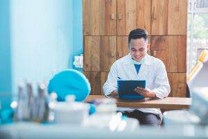 Portrait of happy male dentist or doctor in the clinic wearing lab coat