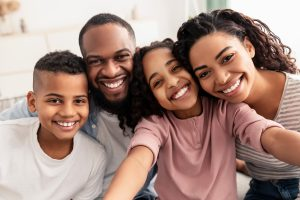 Capturing Moments. Portrait of happy loving black family of four people taking selfie together, closeup. Positive parents posing with their kids and smiling, girl holding camera, pov